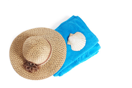 terrycloth: Blue beach towel with broad-brim straw summer hat and sea shell, isolated on white background