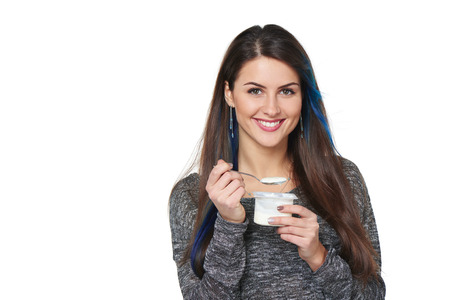 enjoy space: Closeup of smiling healthy woman eating yoghurt isolated on white