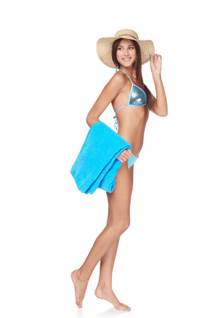 beachwear: Full length of happy beautiful slim tanned woman in blue bikini wearing summer hat holding beach towel, looking away at blank copy space, isolated on white background