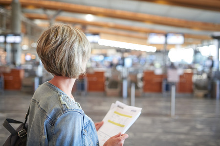 e ticket: Back view of a woman standing in airport hall, holding sheets of e-tickets Stock Photo