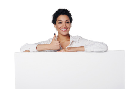 Happy emotional african american business woman standing behind blank white banner, gesturing thumb up, over white background Imagens