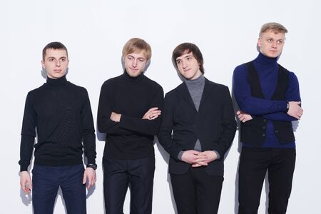 discord: Four young men  standing in full length near the wall, looking in different directions, over white background