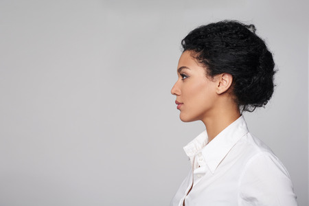 from side: Closeup profile of confident business woman looking forward isolated on gray background Stock Photo