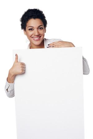 幸せな感情的なアフリカ系アメリカ人ビジネス女性空白の白い旗の後ろに立って、白い背景の上を親指を身振りで示す