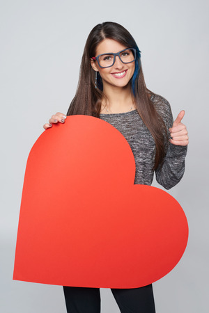 approving: Young happy woman holdin Love symbol - big red heart shape, and showing approving sign