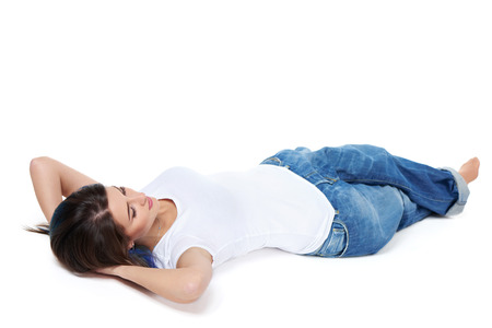 Full length woman lying down at floor on her back with hands over head, having rest, isolated on white background