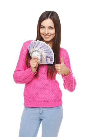 Closeup of young beautiful woman with British pounds in hand gesturing thumb up