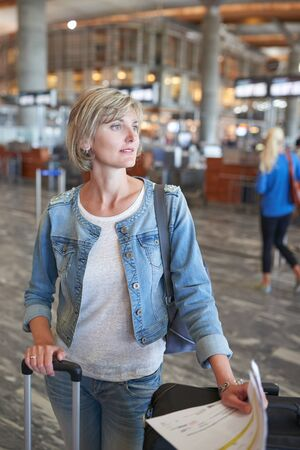 arrive: Woman standing with luggage in airport hall looking out of frame Stock Photo