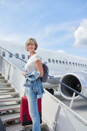 Happy woman standing at plane ladder going to board, outdoors, airport