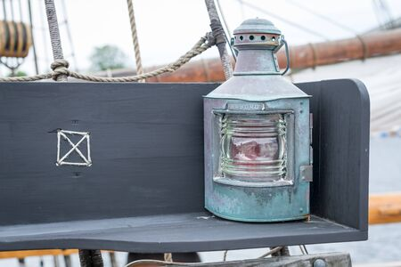 brass lamps: Old copper sailing boats lamp on the bench on yacht Stock Photo