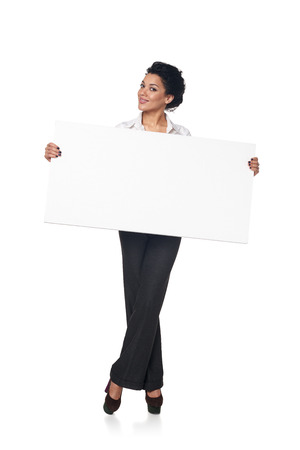 Full length smiling business woman holding blank white board, isolated on white background Stock Photo