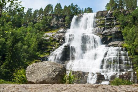 waterfall in the forest: Waterfall Tvindefossen in sunny summer day, Norway. Shallow depth of field, focus at stone on foreground.