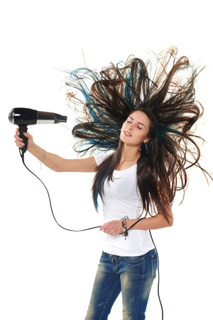 Female drying her hair with hair-drier, flying hair, isolated on white