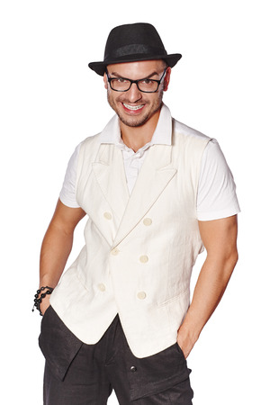 fedora hat: Elegant happy young handsome man wearing white waistcoat and black hat standing with hands in pockets, over white background Stock Photo