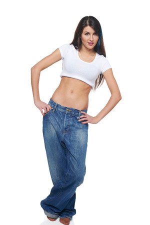 oversize: Beautiful funk girl in oversize jeans standing with hands on hips, over white  Stock Photo
