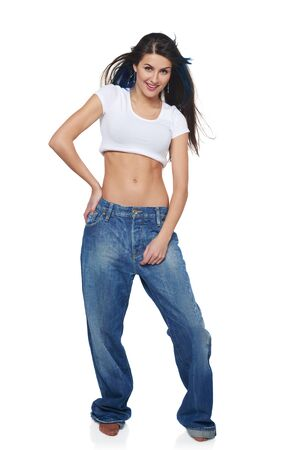 Beautiful funk girl in oversize jeans standing over white with flying hair