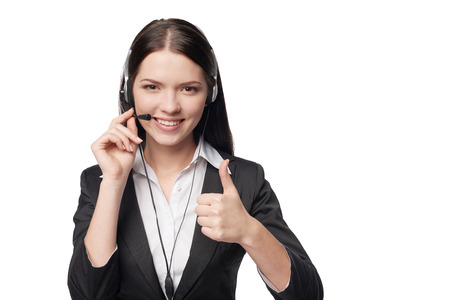 business service: Closeup of happy smiling attractive woman with headphone showing approving sign, isolated against white background Stock Photo
