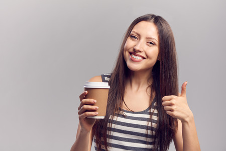 takeaway: Happy smiling young woman holding hot drink from disposable paper cup gesturing thumb up, isolated over gray background, with copy space Stock Photo
