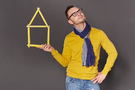 envisioning: Thinking envisioning man holding new house home concept of yellow meter