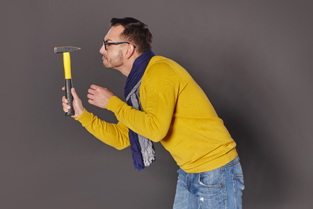 pedantic: Side view of a carping man holding hammer pointing at blank copy space looking very critical