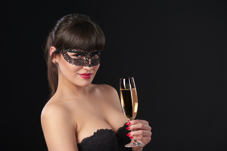 sexy birthday: Sensual woman wearing black masquerade carnival mask at party holding a glass with champagne. Closeup portrait with copy space