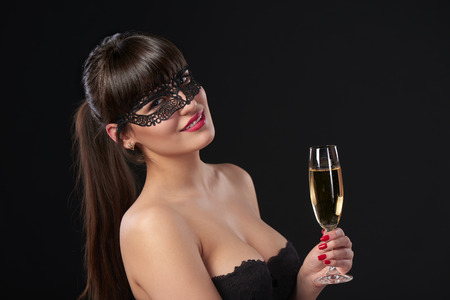 Sensual woman wearing black masquerade carnival mask at party holding a glass with champagne. Closeup portrait with copy space