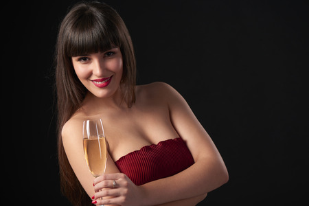 anniversary sexy: Sensual smiling woman holding a glass with champagne. Closeup portrait with copy space