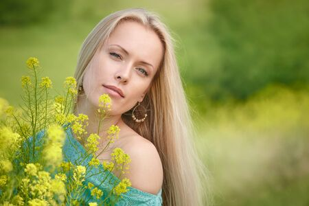 nude outdoors: Closeup portrait of beautiful woman over nature background yellow flowers, shallow depth of field