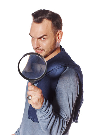 sceptic: Serious man looking through magnifying glass  with a speculative look on his face looking at the camera, over white background. Search concept.