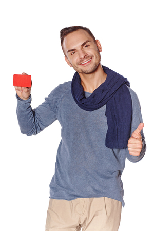 Smiling trendy casual man showing blank credit card and gesturing thumb up, over white background photo
