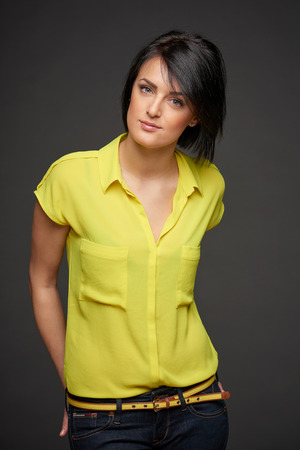 Confident relaxed woman over dark studio background