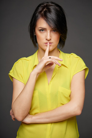 Serious young business woman with finger on lips, half length portrait photo