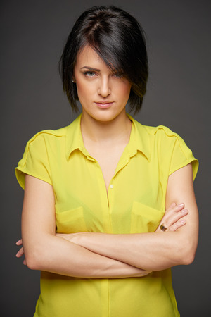 brooding: Confident woman staring deeply at you with her arms crossed Stock Photo