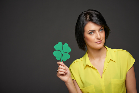 St.Patricks day holiday. Beautiful woman holding green paper shamrock leaf in hand, over gray background. Horizontal shot with copy space photo