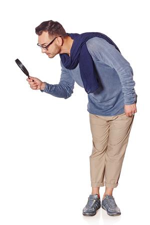 検索の概念。全長深刻な男を空白のコピー スペースで虫眼鏡を見下ろす、白い背景の側面図です。