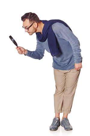 Search concept. Side view of full length serious man looking through magnifying glass at blank copy space down, over white background.