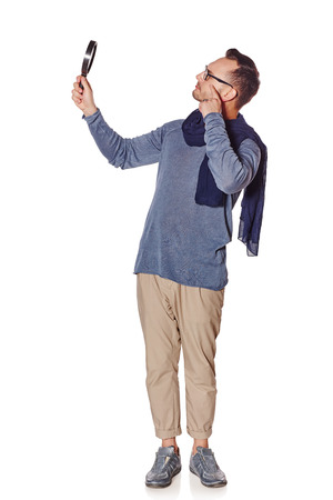 sceptic: Search concept. Side view of full length serious man looking through magnifying glass at blank copy space, over white background.