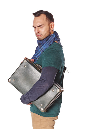 sullen: Sullen sad man with suitcase under his arm pulling his face in disgust, over white background Stock Photo