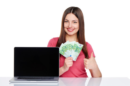 great deal: Smiling woman showing laptop computer screen holding euro money in hand gesturing thumb up, isolated on white background