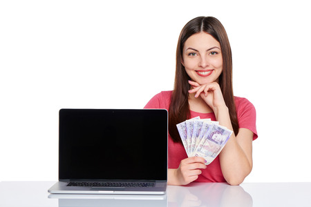 Smiling woman showing laptop computer screen holding British pounds in hand, isolated on white background