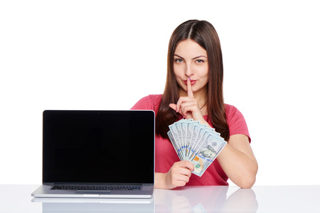 conspiratorial: Smiling woman showing laptop computer screen holding British pounds in hand and gesturing finger on lips, isolated on white background