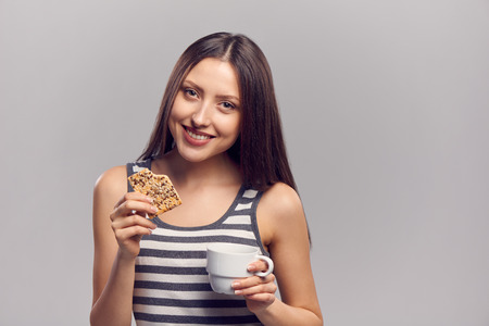 enjoy space: Beautiful young woman drinking hot drink from disposable paper cup with a biscuit, isolated over gray background, with copy space