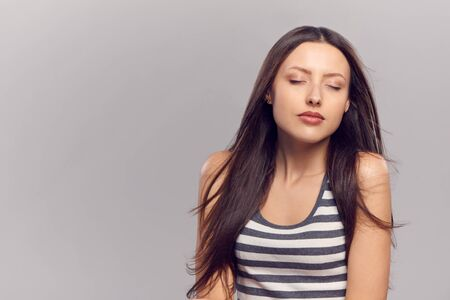 closed eye: Young woman enjoying with eyes closed, over gray  background