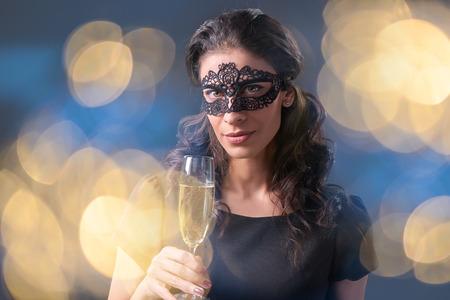 sektglas: Sinnliche Frau, die schwarze Maskerade Faschingsmaske an die Partei mit einem Glas mit Champagner über Urlaub Bokeh Hintergrund. Detailansicht-Porträt mit Kopie Raum