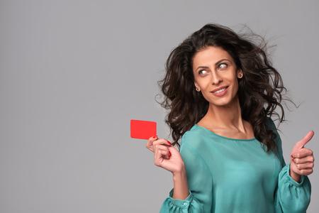 tarjeta de credito: Retrato de la mujer sonriente joven que sostiene la tarjeta de crédito en blanco y haciendo gestos pulgar hacia arriba, mirando hacia el lado en el espacio de la copia en blanco, sobre fondo gris