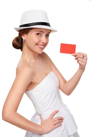 fedora hat: Happy smiling woman in white summer dress and a hat, showing blank credit card, on white background
