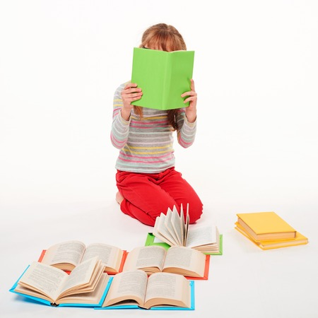 Prodigy: Little girl sitting on the floor with a lot of books, covering the face with a book reading, over white background
