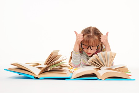 assiduous: Eureka. Excited little girl lying on stomach on the floor with a lot of opened books in front of her, giving double thumbs up, over white background