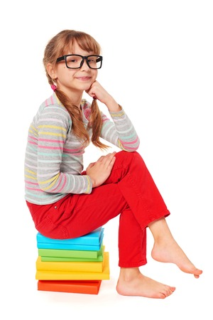 reading materials: Little girl sitting on the pile of multicolor books, making proud satisfied face, over white background
