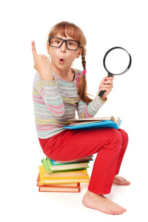 prodigy: Search concept. Surprised little girl sitting on the pile of multicolor books, holding magnifying glass, over white background Stock Photo